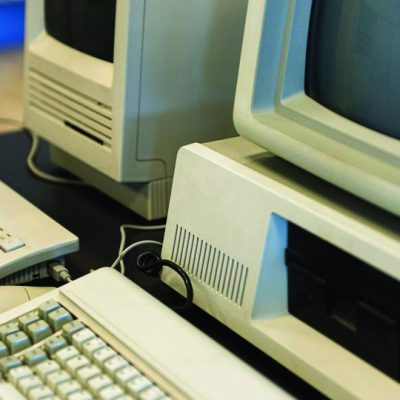 Two computers from the 1980s stand side by side in an office.